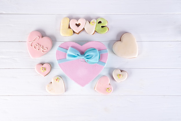 クッキーとバレンタインの日の白い木製の背景にバラのハートボックス