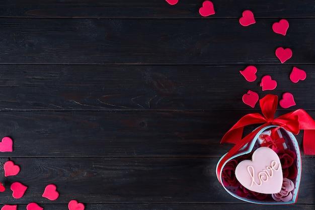 暗い背景の木のハートボックスにハートの形のバレンタインのクッキー
