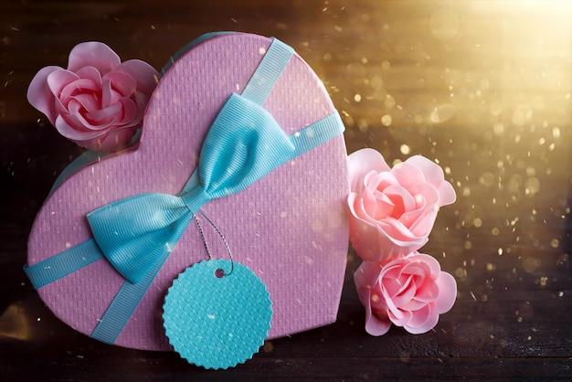 聖バレンタインの日ボックスハートと暗い背景の木、コピー領域にピンクのバラ