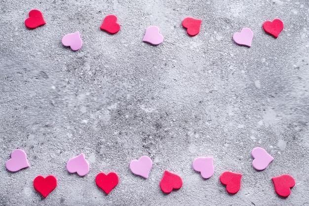 Красные и розовые сердца на фоне камень. валентина фон для открытки