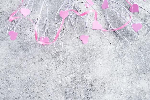 コンクリートの背景にピンクの心と雪の中で枝
