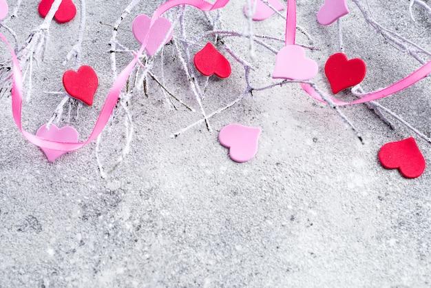 コンクリートの背景にピンクと赤の心と雪の中で枝
