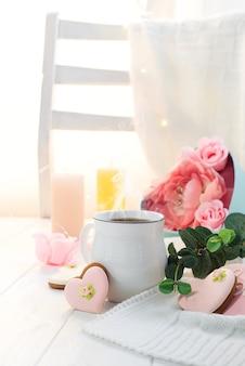 ベッドでロマンチックな朝食。コーヒー、クッキー、ギフト用の箱、木製のテーブルの上に花。バレンタインデーのコンセプト