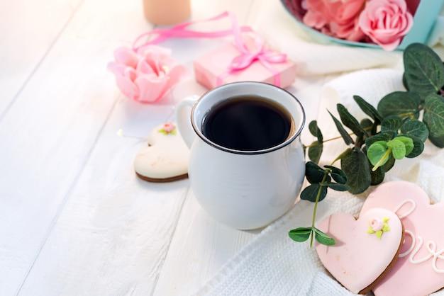 コピースペースと格子縞の木製の背景にコーヒーのカップとハートクッキー