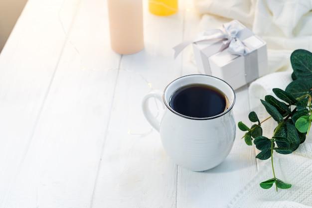 コピースペースのベッドの中の木製トレイに滞在してニットスカーフとコーヒーのカップ。おはよう朝食
