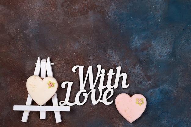 Печенье в форме сердечка на глазури на мольберте в виде рисунка. с днем святого валентина