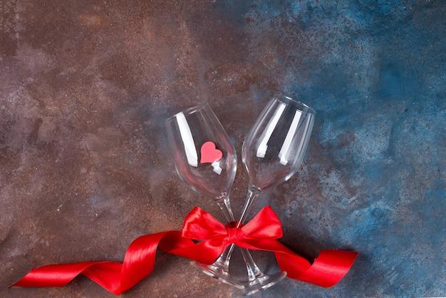 Празднование дня святого валентина с двумя стаканами и красной лентой на каменном фоне