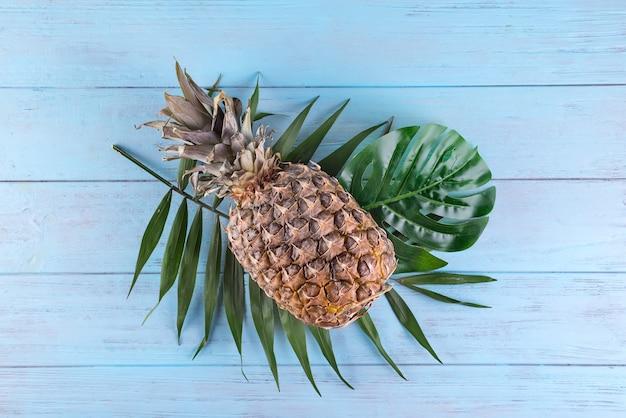 パイナップルと熱帯のヤシの葉の青い木製の背景