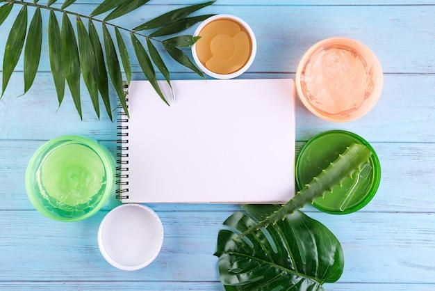 カタツムリ、アイパッチ、青い木製の背景に紙のノートと瓶の中のアロエベラジェルのゲル。コピースペース