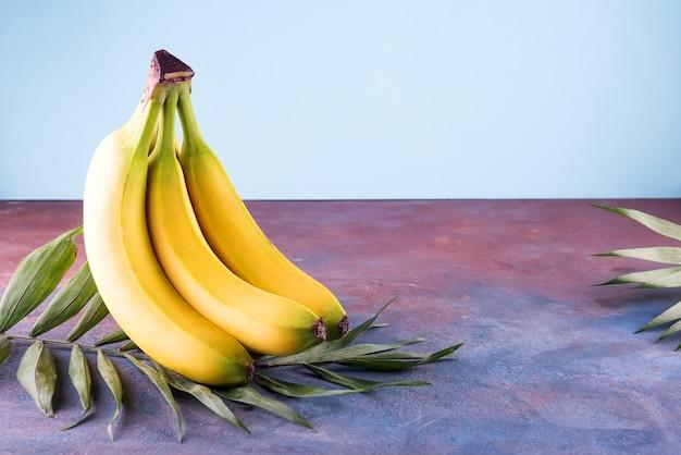 Гроздь бананов с пальмовых листьев на фоне каменных с копией пространства