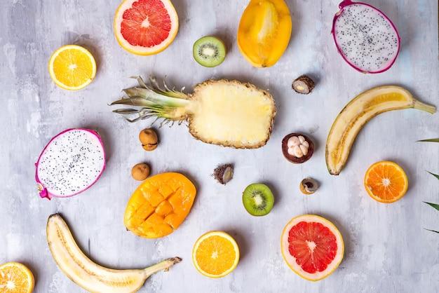 Ассортимент тропических фруктов на камне светлом фоне картины. вид сверху. копировать пространство