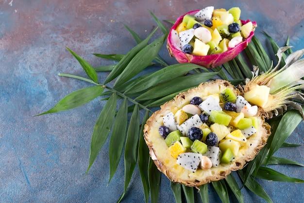 エキゾチックなフルーツサラダは、石の背景にヤシの葉の上にパイナップルの半分で提供しています。健康食品
