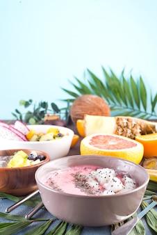 Красные или розовые чаши асаи со смузи, увенчанные свежими семенами питайи и чиа на пальмовых листьях на каменном фоне, скопируйте пространство