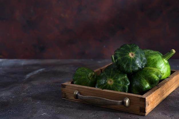 暗い背景の木の木製の箱で小型パティパンパティソンスカッシュ
