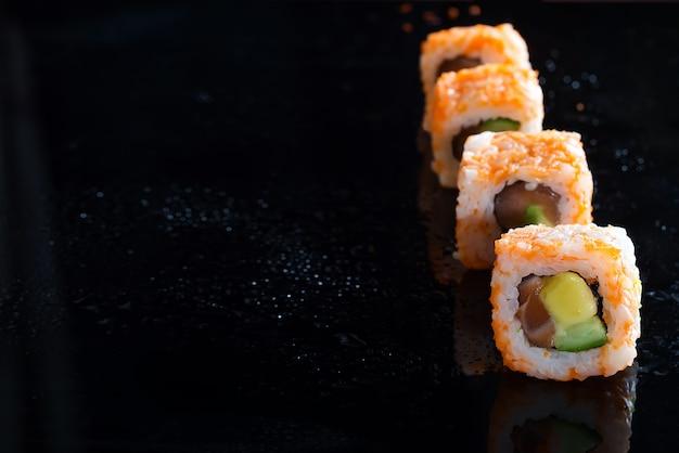 カニ肉、アボカド、キュウリのガラスの黒い背景に作られたカリフォルニアマキ寿司ロール