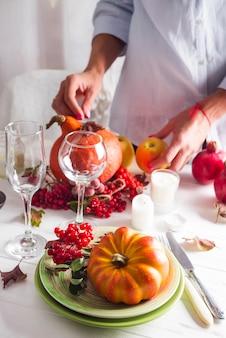 女の子の手が感謝祭のお祝いテーブルの設定を準備する