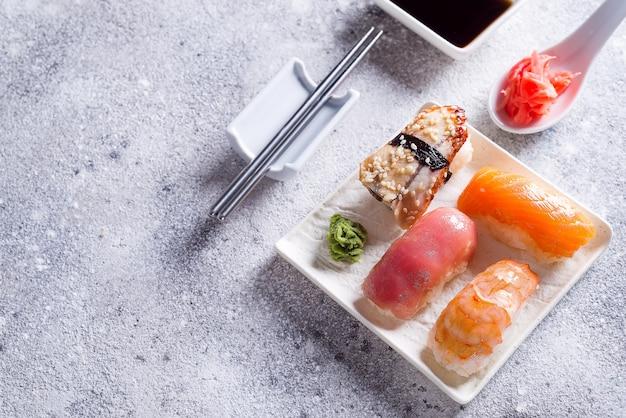 平らな石の背景、光石の背景に金属の韓国の棒でセラミックプレートに様々な寿司