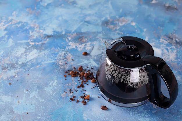 コーヒー豆でいっぱいのコーヒーメーカーポット