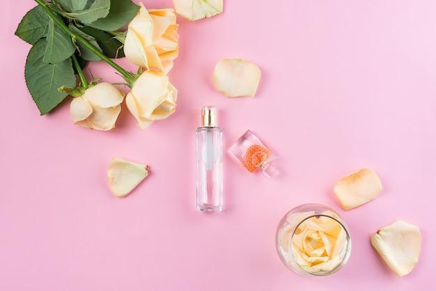 ピンクの背景の花の香水瓶。香水、化粧品、フレグランスコレクション。フラットレイ