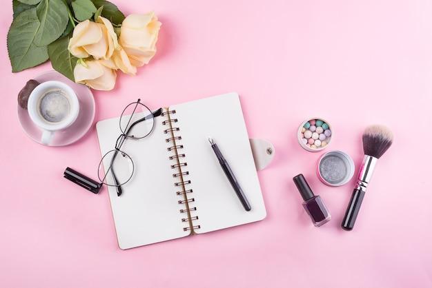 ノートブック、メガネ、バラとアクセサリーの職場のモックアップ