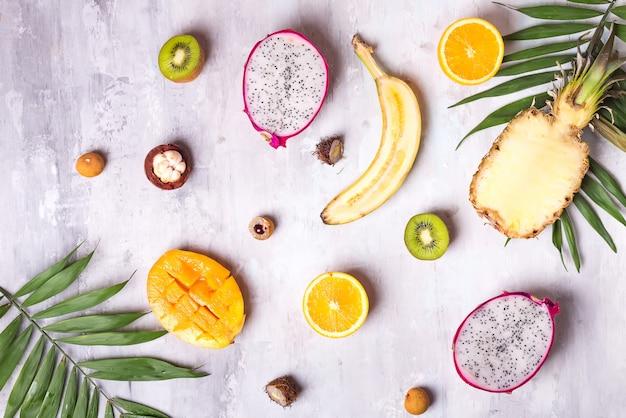 果物とヤシの葉が白い背景に。トロピカルフルーツ