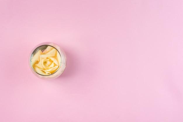 コピースペースとピンクの背景の瓶に白いバラ