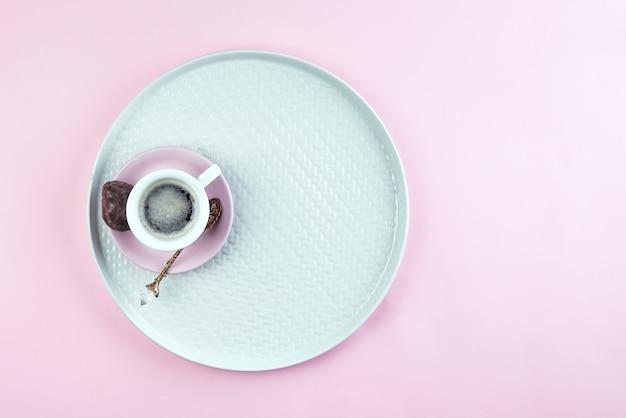 ピンクの紙の背景、上面の皿の上の香りのコーヒーカップ