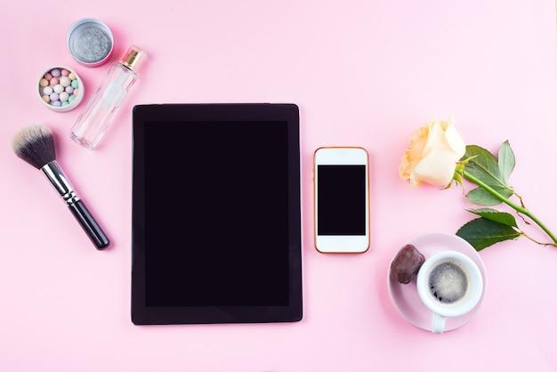 Плоский набор лежал планшета и телефона с чашкой кофе, очки, роза и духи на розовом, макет
