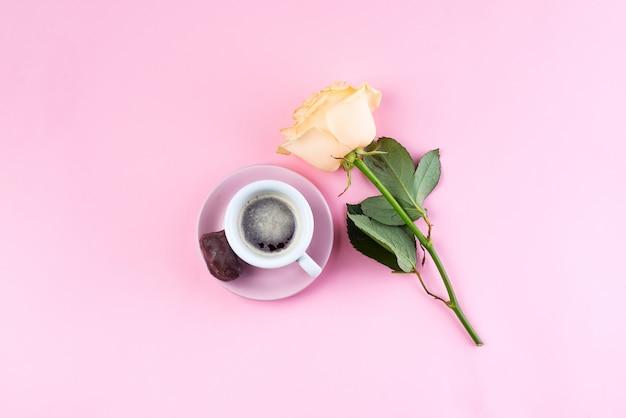 コーヒーの新鮮なカップとパステルピンクの背景、平らにベージュの香りのバラ