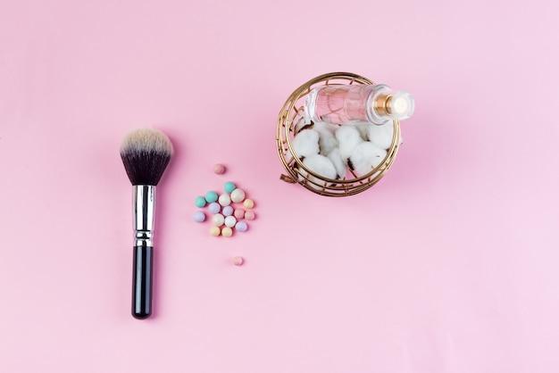 綿、香水、ピンクの背景のブラシのカラフルな化粧品ボールのセット。