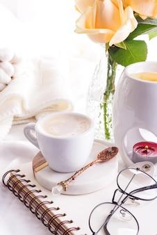 朝のコーヒーマグ、ノート、キャンドル、ローズのグラス