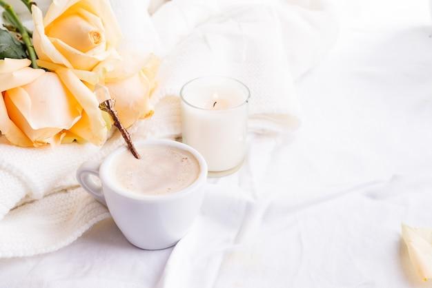 朝のロマンチックなコーヒーはぼろぼろのシックなスタイルのインテリアにベージュのバラの花束と一緒にベッドに役立った