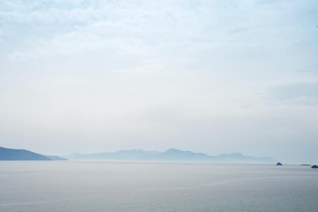 霧の多い山々に対する海の美しい神秘的な自然の背景