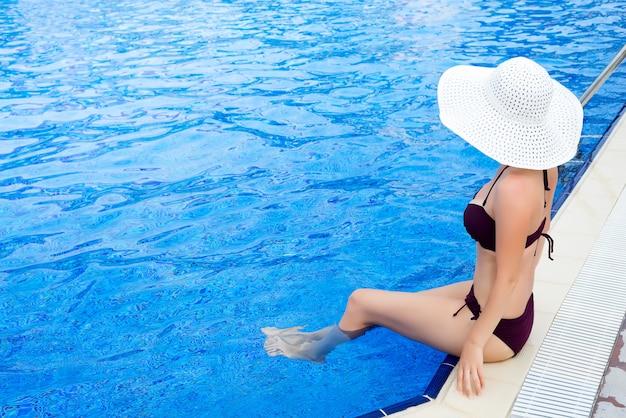 白い帽子とプールの青い水で日光浴で美しい女性。夏の背景