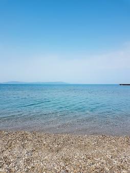 自然水面と小石のビーチ。小石のビーチと海の水の背景。