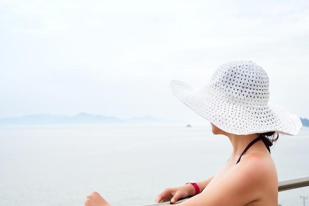 白い帽子で美しい少女は、晴れた日に海と山々を見ています。夏休み