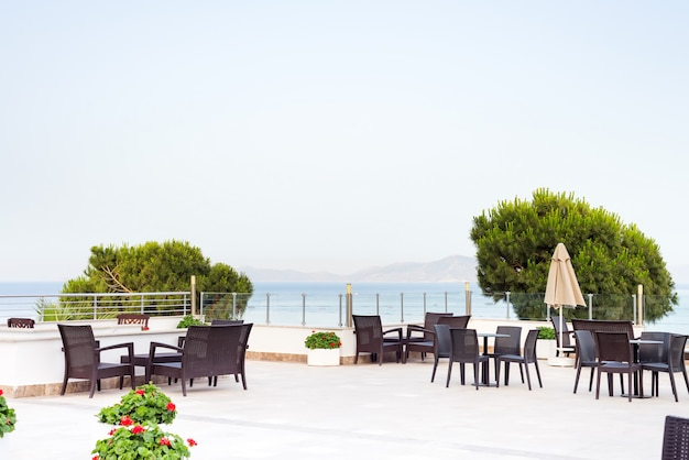 Уютный плетеный столик в открытом кафе-баре на крыше утром с видом на море,