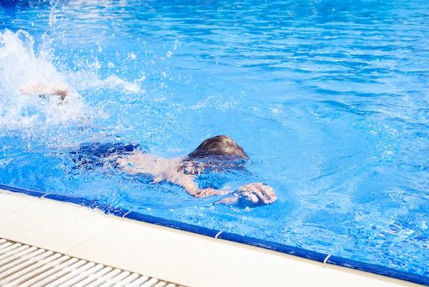 水泳パンツ姿の少年は夏休みに青い水プールで泳ぎます。