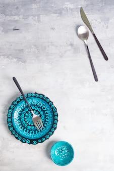 Турецкая керамика украшена синей тарелкой и миской с новыми роскошными черными столовыми приборами на каменном фоне, вид сверху