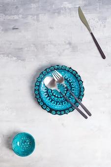 トルコの陶器は青いプレートと新しい豪華な黒のカトラリーとボウルを装飾