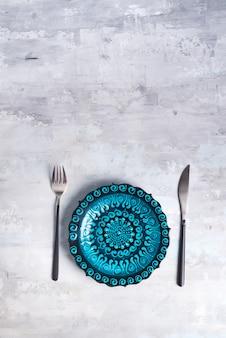 トルコの陶器は、新しい高級黒カトラリーで青いプレートを飾った