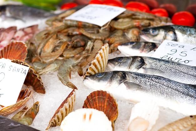 カウンターで氷の上で販売するための新鮮な魚、イカ、イカ、エビ
