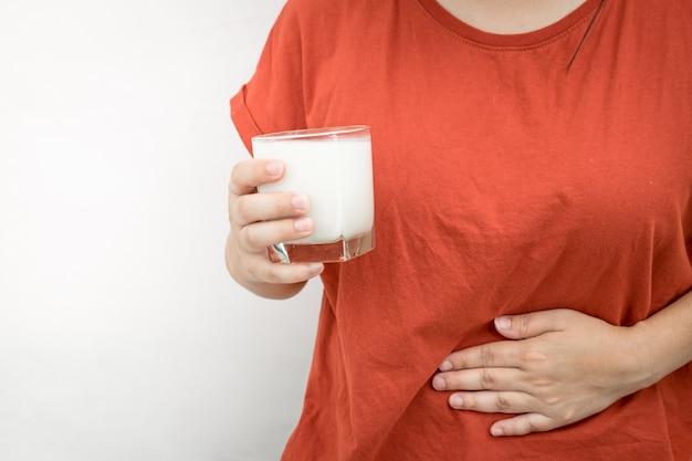 Молодая женщина чувствует боль в животе после выпить немного молока. рука держит стакан молока на белом.