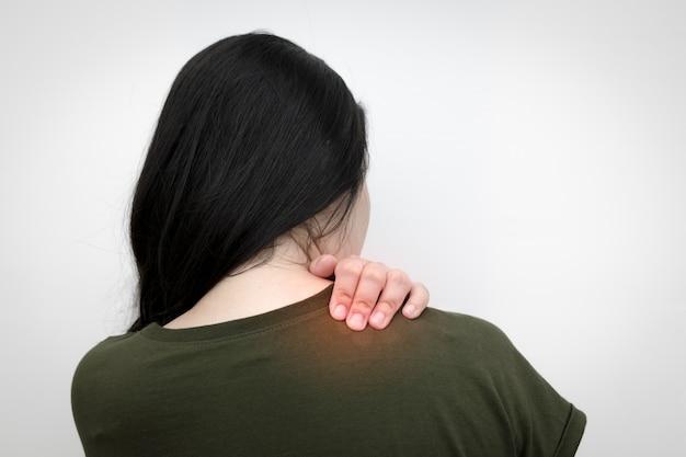 Боль в плече женщины, рука нажимает на плечо, чтобы расслабить напряжение мышц