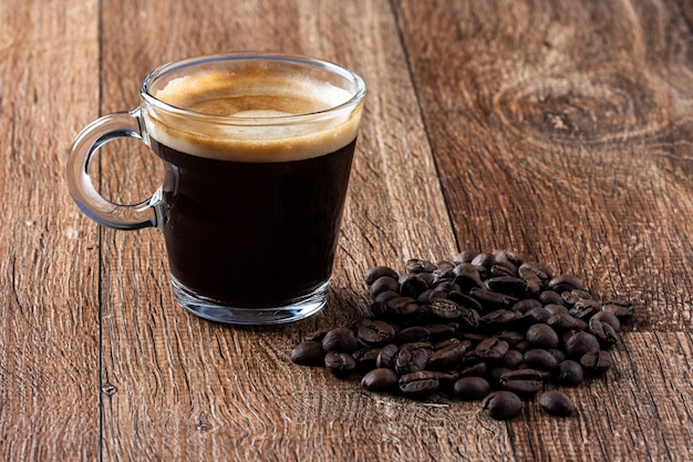 コーヒー豆やカフェ・エ・マデイラと木製のテーブルの上のコーヒー