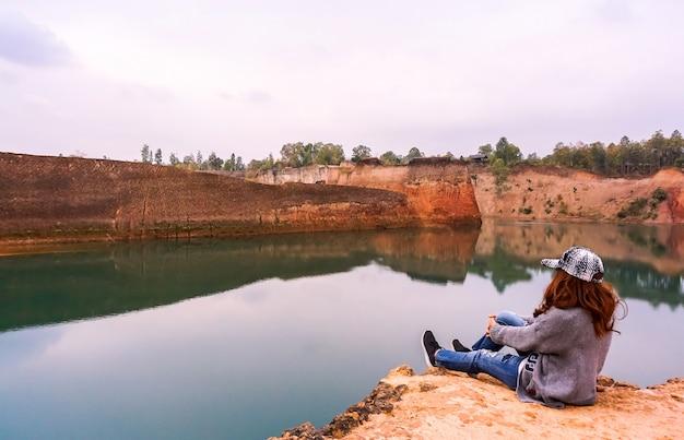 崖の端に座っていた女性。自然で美しいものを見る