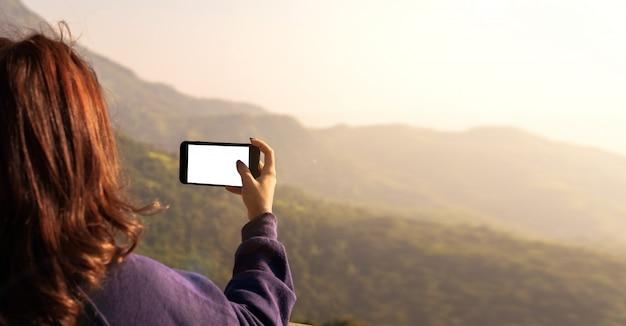 女性は自然の写真を携帯電話で撮っています。