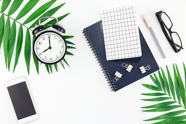 アラーム、ノートブック、スマートフォン、葉が付いたスタイルのデザインオフィスワークスペースデスク