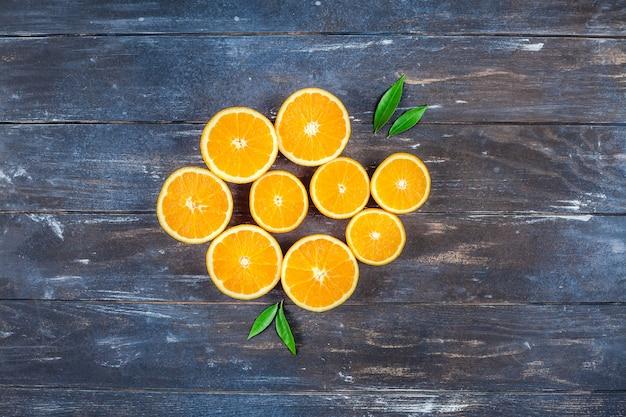 Свежие апельсины на темном деревянном столе