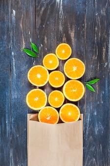 暗い木製のテーブルに新鮮なオレンジ
